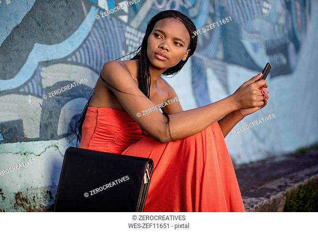 Woman sitting at graffiti wall with cell phone and folder