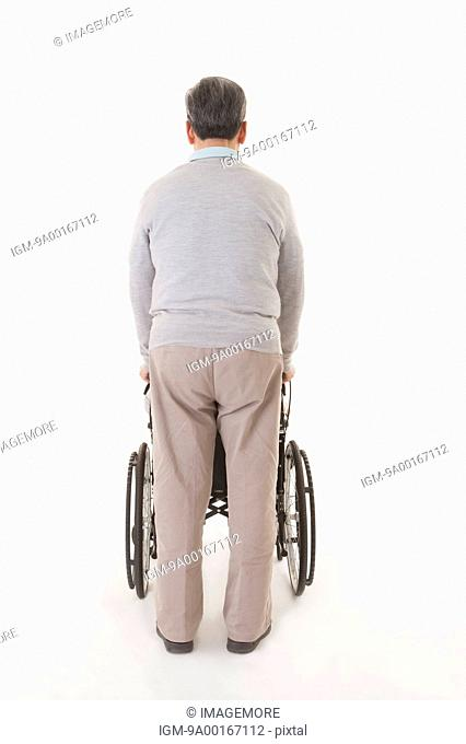 Senior man pushing wheel-chair with rear view