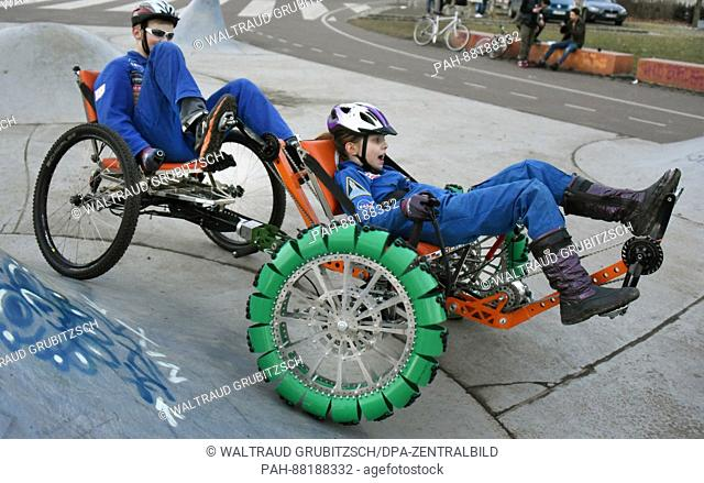 Cosma (r) and Jonas test a moonbuggy with wheels without air pressure at the Leipzig International Space Education Institute (ISEI) in Leipzig, Germany