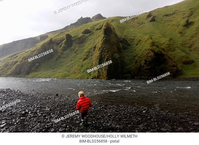 Caucasian boy was standing near rocky river