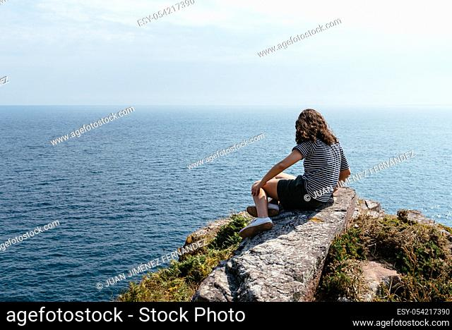 Beautiful woman on cliffs looking at seascape in Cap Frehel area, Brittany, France. Atlantic ocean french coast