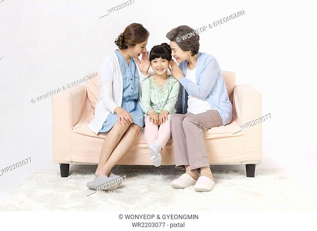 Mother and grandmother whispering to young girl all seated on a couch and smiling