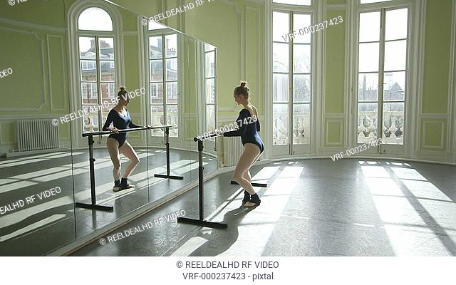 Female Ballet Dancer stretches and practices using the barre and studio mirror