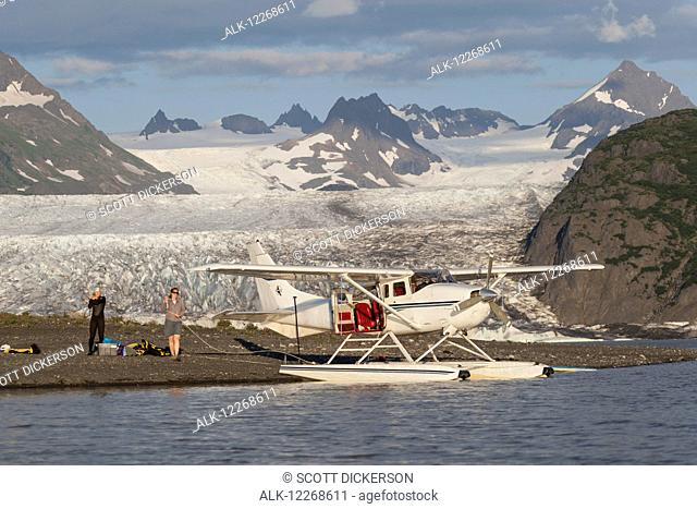 People unloading gear from a floatplane in front of Grewingk glacier in Kachemak Bay State Park, Southcentral Alaska