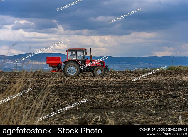 Tractor spreading artificial fertilizers at summer
