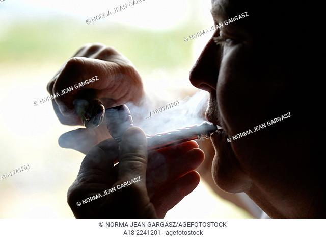 A renal patient smokes medicinal marijuana to alleviate pain