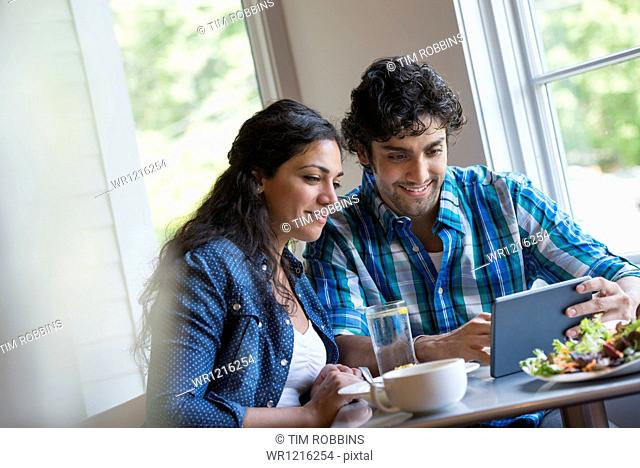 A couple seated looking at a digital tablet