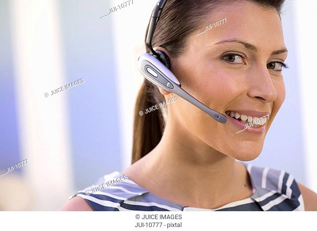 Woman in headset, smiling, portrait, close-up