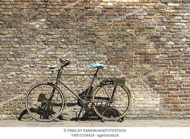 Old styled bike abandoned against an old brick wall, back streets, Bruges, Belgium