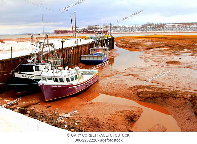 Boats at a wharf at Blomidon, Nova Scotia, Canada in winter at low tide showing snow and mud