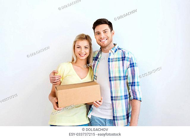 people, delivery, mail, shipping and moving concept - smiling couple with cardboard box
