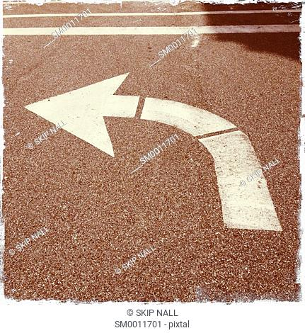 An arrow in the street indicating to take a left hand turn