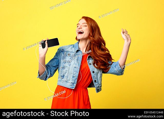 Lifestyle and Music Concept: Beautiful young curly red hair woman in headphones listening to music and dancing on vivid yellow background