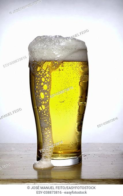 Glass of beer with bubbles and foam overflowing on white on wood and white background