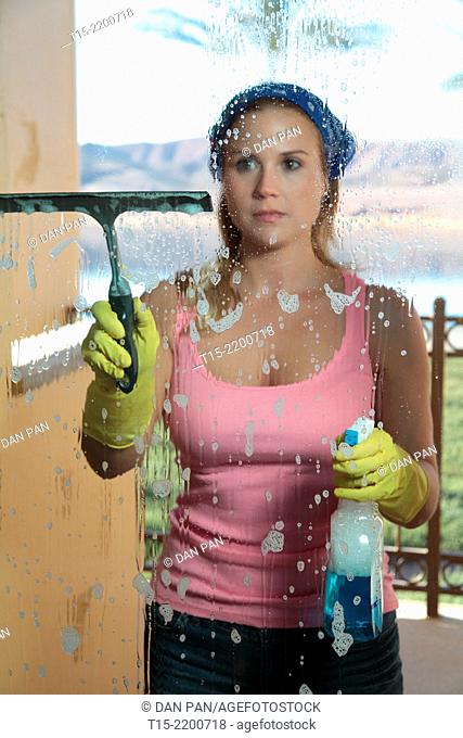 A young woman cleaning the window