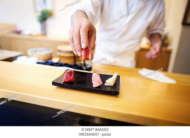 A chef working in a small commercial kitchen, an itamae or master chef presenting a fresh plate of sushi