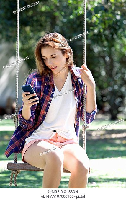 Young woman sitting on swing, looking at smartphone