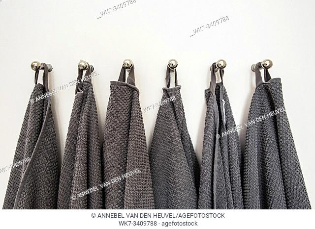 Grey towels hanging in a row, prepared on hanger. white wall close-up