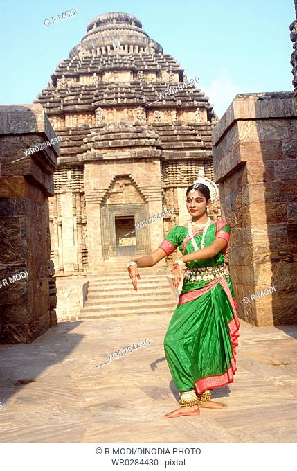 Dancer performing classical traditional odissi dance in front of Konarak Sun temple , Konarak , Orissa , India MR 736D