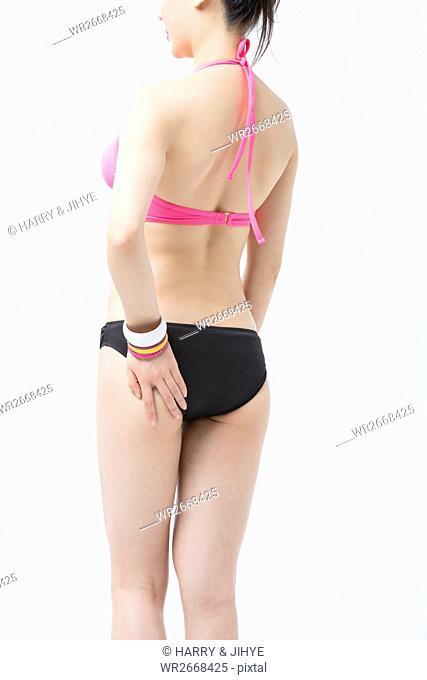 Back of young slim woman in bikini