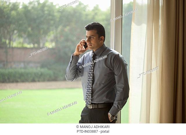 India, Businessman talking on mobile phone in house