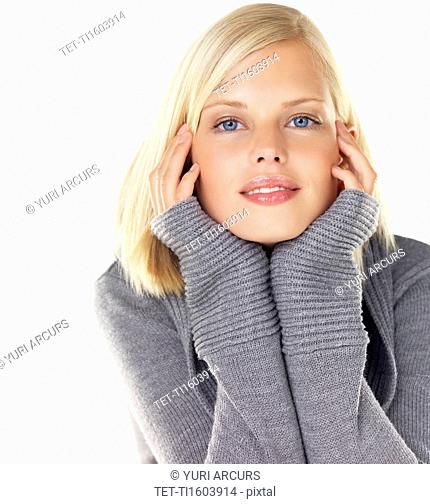 Studio portrait of young woman wearing gray sweater
