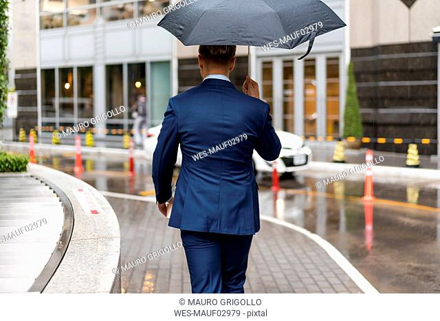 Rear view of young businessman with umbrella during a rainy day in Bangkok