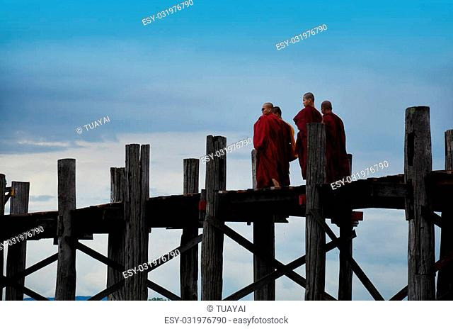 Monk of Burma walking cross over lake at U Bein Bridge