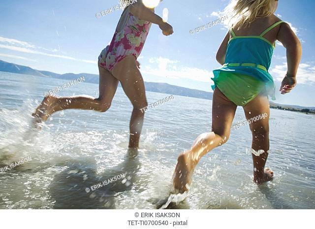 Sisters running in water, Utah, United States