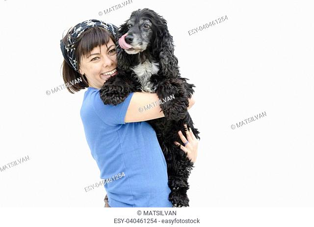 Woman hugging her black cocker spaniel dog with white background
