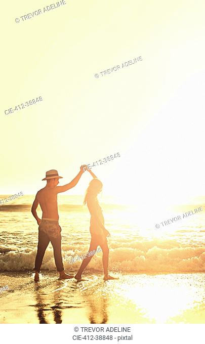 Young couple holding hands, walking on sunny summer sunset ocean beach