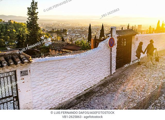 Couple walking at sunset through the alleys of the Moorish Albaicin quarter with Granada overview in background. Granada, Spain