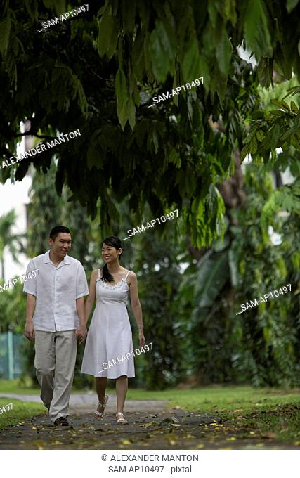 Singapore, Man and woman holding hands in park