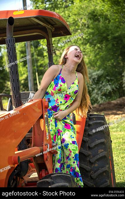 A laughing 14 year old brunette girl wearing a long colorful dress standing on a tractor
