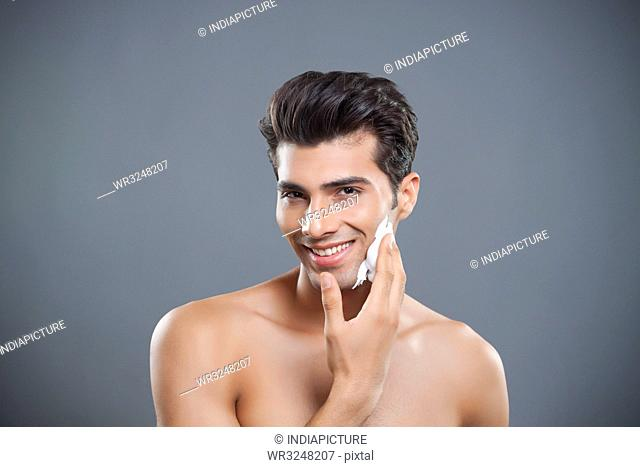 Portrait of young man applying shaving cream