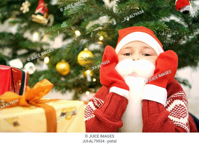 Boy in Santa Claus costume with gift and Christmas tree