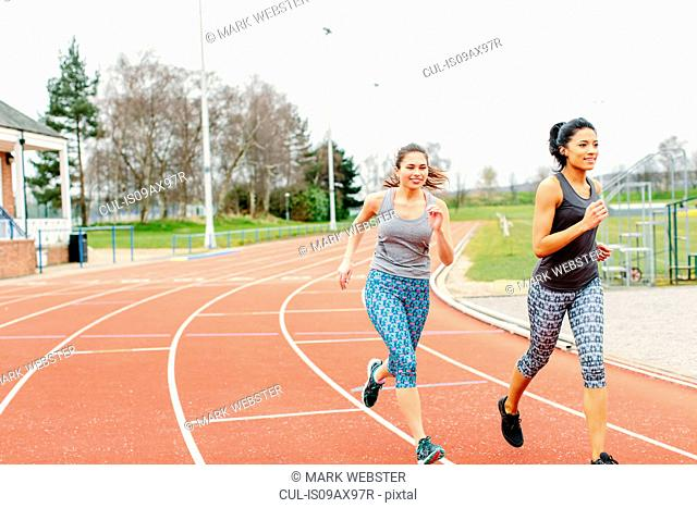 Two young women running on running track