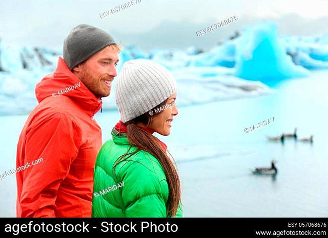 Hiking people visiting Jokulsarlon glacial lagoon / glacier lake on Iceland. Happy tourists on travel enjoying beautiful Icelandic nature landscape in edge of...