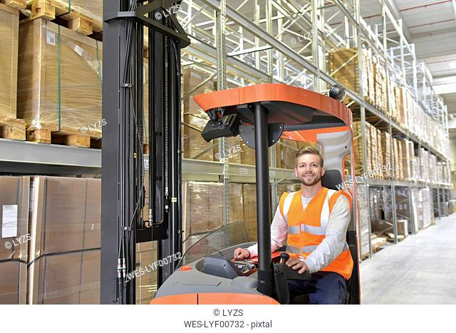Portrait of smiling man in factory hall on forklift