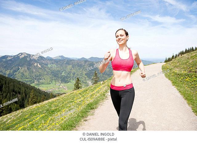 Female jogger running on hilltop