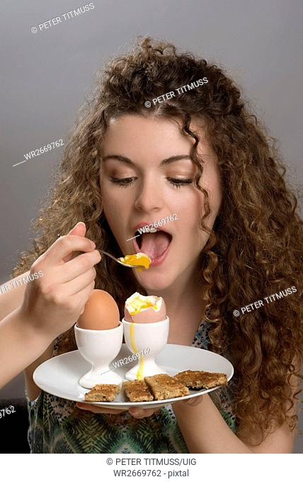Young girl eating boiled eggs for breakfast