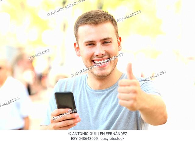 Man with thumbs up holding phone looking at you on the street
