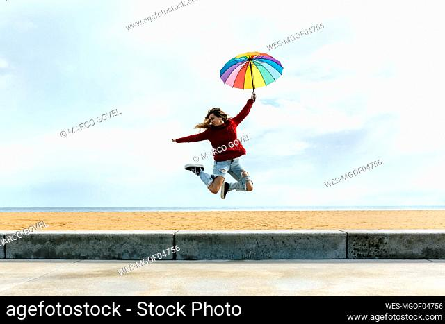 Woman holding umbrella with hand raised while jumping in front of cloudy sky at beach