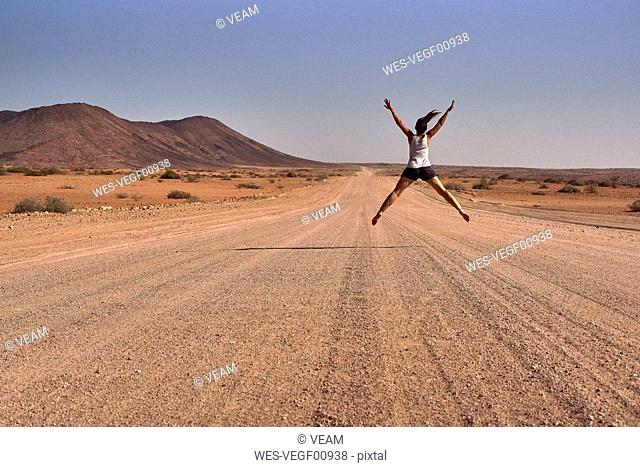 Woman jumping in the middle of a dirt road, Damaraland, Namibia