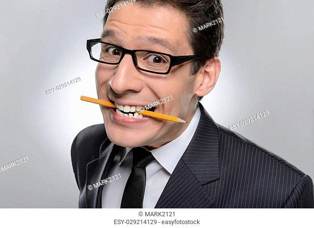 Displeased businessman. Portrait of businessman holding a pencil in his mouth and looking at camera