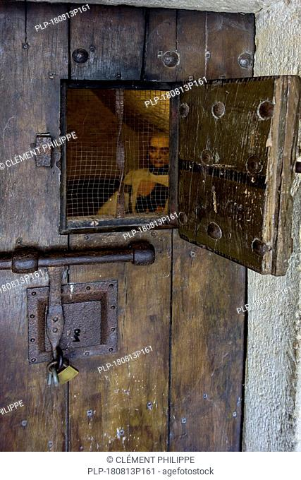 Heavy wooden medieval prison cell door with open hatch showing prisoner in the Château de Bouillon Castle, Luxembourg Province, Ardennes, Belgium