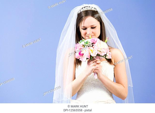 Young woman in wedding gown holding flowers