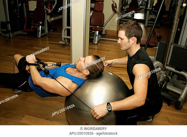 Man working out on exercise ball with spotter