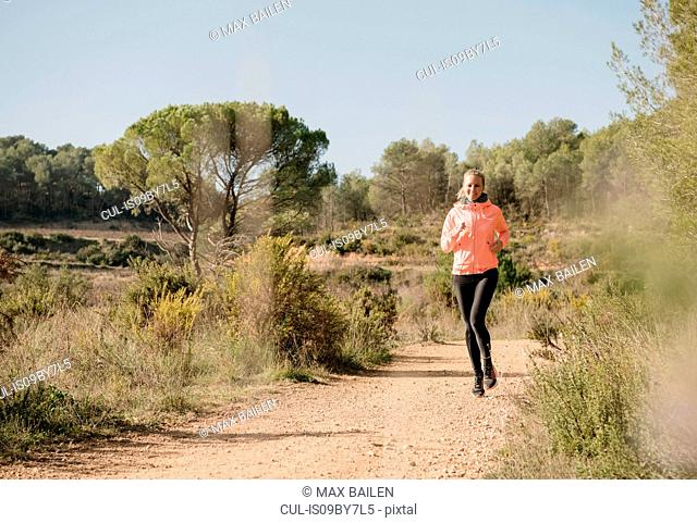Woman jogging on dirt track, Olivella, Catalonia, Spain