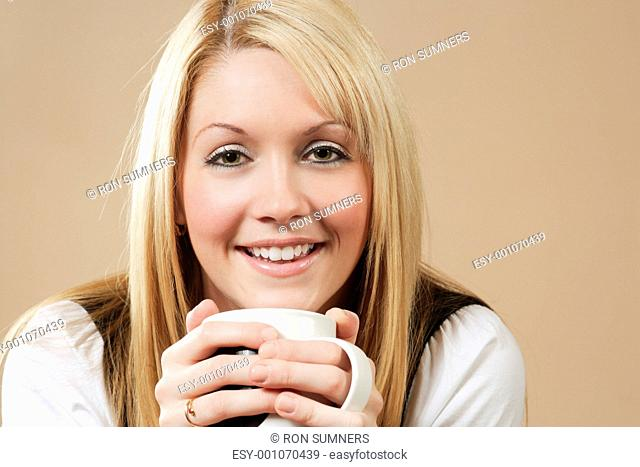 Beautiful blond drinking from a cup